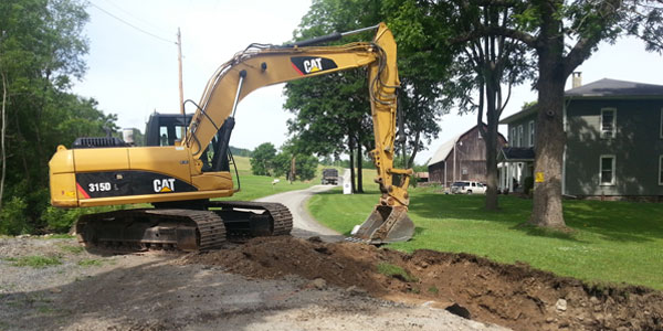 A backhoe digging up some dirt holes in the ground